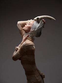 Gotycka kobieta z historyczną koronkową suknią z rogami na głowie, akultyzm, wizerunek halloween