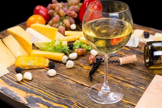 Gourmet food martwa natura - zbliżenie kieliszek białego wina wśród różnych serów i świeżych owoców na rustykalnym drewnianym stole z miejscem na kopię