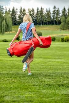 Gowomen czas gry w golfa trzymając sprzęt golfowy na zielonym polu