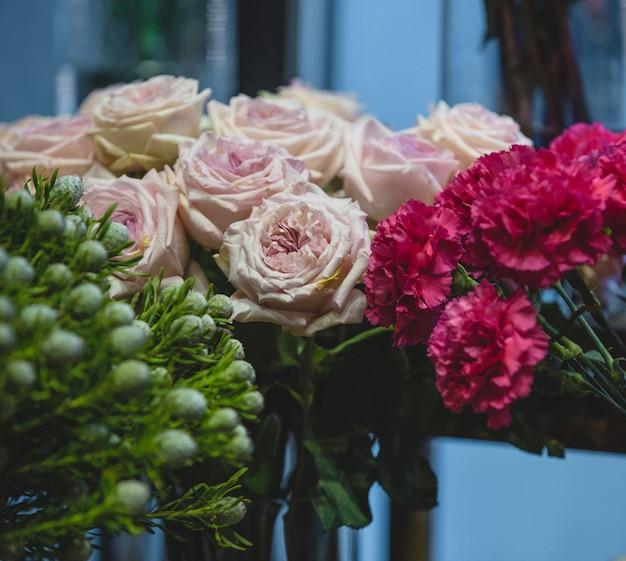 Goździki fuscia, różowe róże i zielone kwiaty w jednym ujęciu