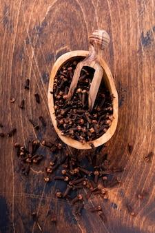 Goździki. sucha przyprawa do gotowania i napojów na prostym starym drewnianym tle. selektywne skupienie.