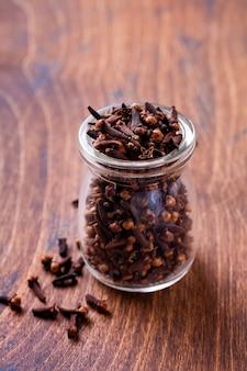 Goździki. sucha przyprawa do gotowania i napojów na prostym starym drewnianym tle. selektywne skupienie