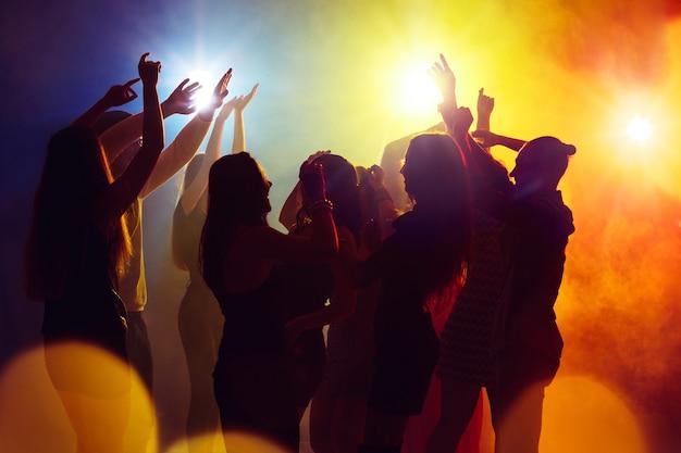 Gra aktorska. tłum ludzi w sylwetce podnosi ręce na parkiecie na neonowym tle. życie nocne, klub, muzyka, taniec, ruch, młodzież. żółto-niebieskie kolory i poruszające dziewczyny i chłopcy.