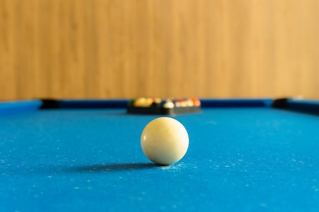Gra bilardowa. biała piłka na miejscu z ustalonymi kolorami piłka w tle na błękita stole.