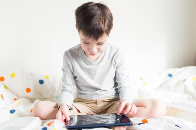 Gra. chłopiec bawi się smartfonem. school boy na łóżku w domu z cyfrowego tabletu w ręku, odrabiania lekcji. edukacja online na odległość. kwarantanna. gra. chłopiec bawi się smartfonem