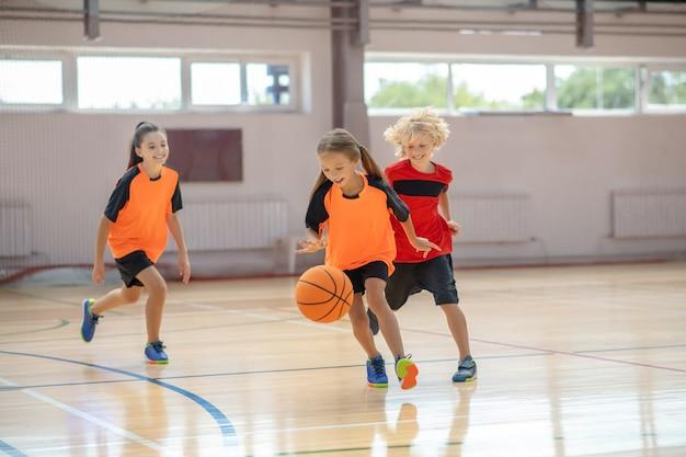 Gra. dzieci w jasnych strojach sportowych grające w koszykówkę i biegające za piłką