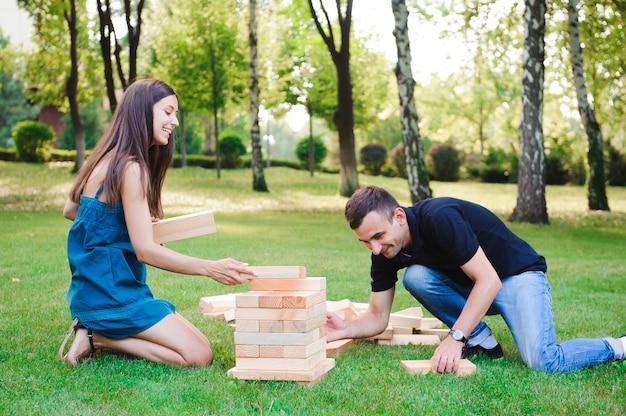 Gra grupowa polegająca na umiejętnościach fizycznych z dużymi blokami na zielonej trawie.