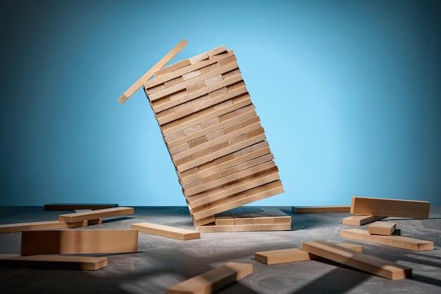 Gra jenga, spadająca wieża z drewnianych klocków na niebiesko