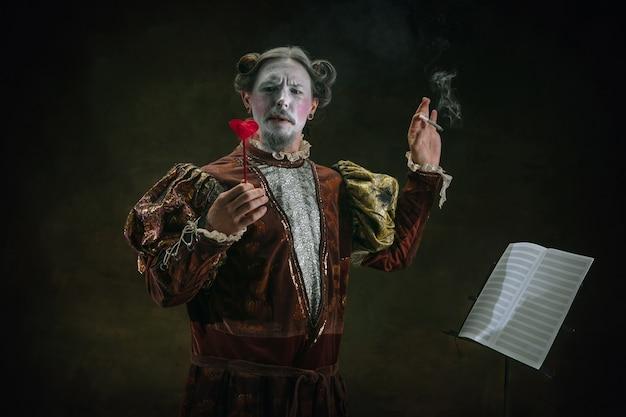 Gra na skrzypcach młody mężczyzna jako johann bach na ciemnozielonym tle