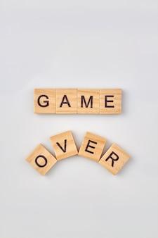 Gra nad koncepcją. koniec gry napisany drewnianymi kostkami na białym tle.