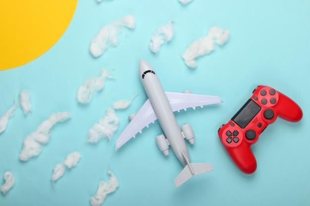 Gra powietrzna. gamepad, zabawka samolot na słonecznym niebie z chmurami