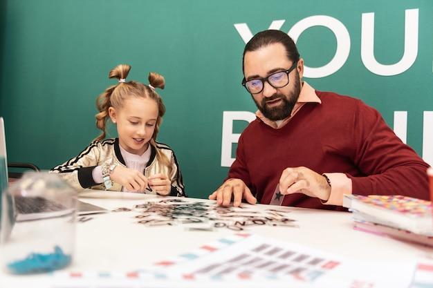 Gra słów. śliczna jasnowłosa dziewczyna nosząca bransoletki na dłoni, tworząca słowa z listów ze swoim nauczycielem