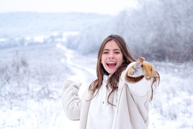 Gra snowball w szczęśliwą zimę. zabawa ze śniegiem i zabawa w winter park. aktywność uśmiechnięta dziewczyna w podróży zimą.