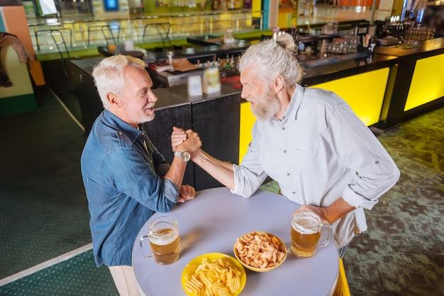Gra w armwrestling. pozytywni starsi mężczyźni uprawiający armwrestling podczas rozrywki