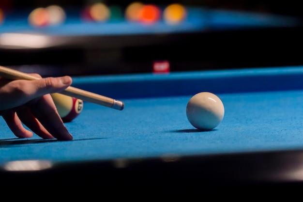 Gra w bilard. kule bilardowe i kij na niebieskim stole bilardowym