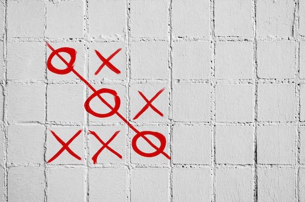 Gra w kółko i krzyżyk na betonowej ścianie z białych płytek