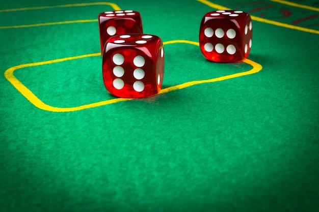 Gra w kości na zielonym stole do gry. gra w kości. czerwone kości w kasynie. rzut kostką do gry