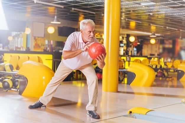 Gra w kręgle. miły starszy mężczyzna przygotowuje się do rzucenia piłką podczas gry w kręgle