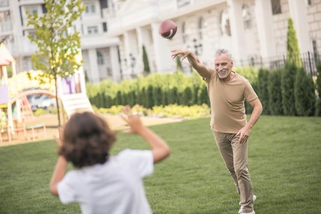 Gra w piłkę. ciemnowłosy chłopiec grający w piłkę z tatą