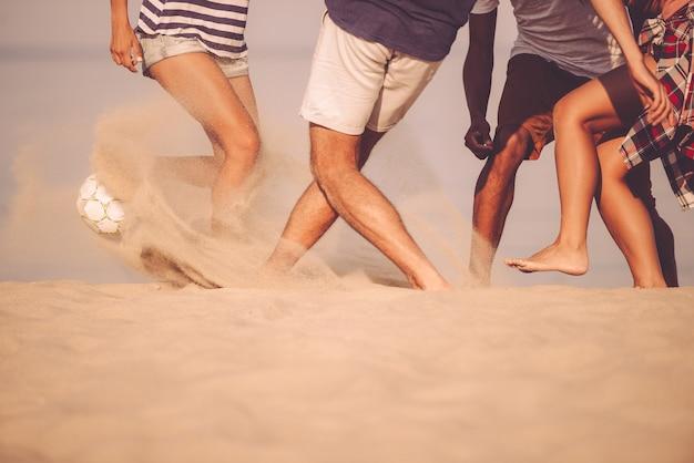 Gra w piłkę plażową. przycięty obraz młodych ludzi bawiących się piłką nożną na plaży