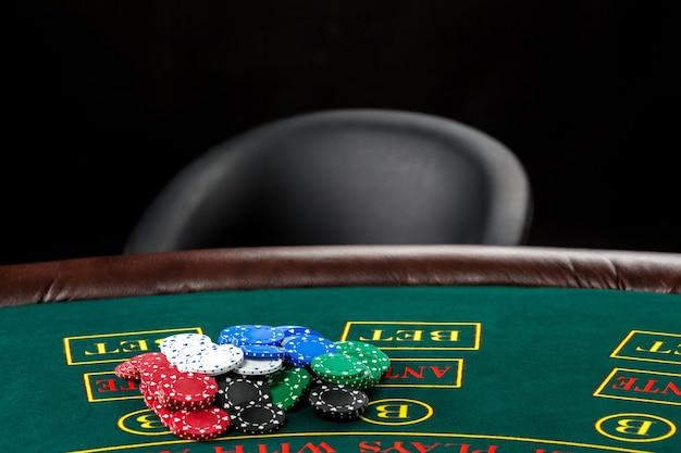 Gra w pokera. frytki na zielonym stole i pustym krześle