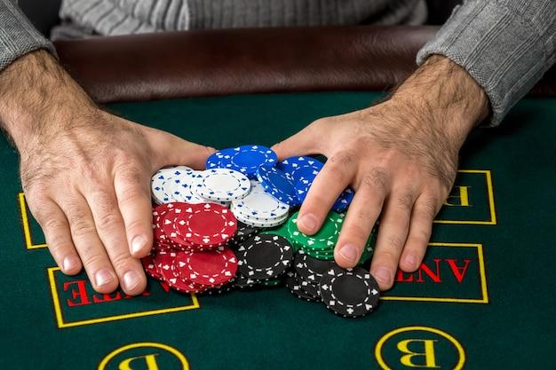 Gra w pokera. żetony na zielonym stole. żetony w męskich rękach