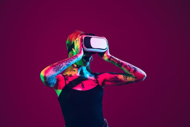 Gra z zestawem słuchawkowym vr. młoda kobieta kaukaski na fioletowym tle studio w świetle neonowym. piękna modelka z tatuażami. ludzkie emocje, wyraz twarzy, sprzedaż, koncepcja reklamy. kultura dziwaka.