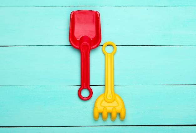Grabie i łopata dla dzieci do piaszczystej plaży na niebieskim drewnianym