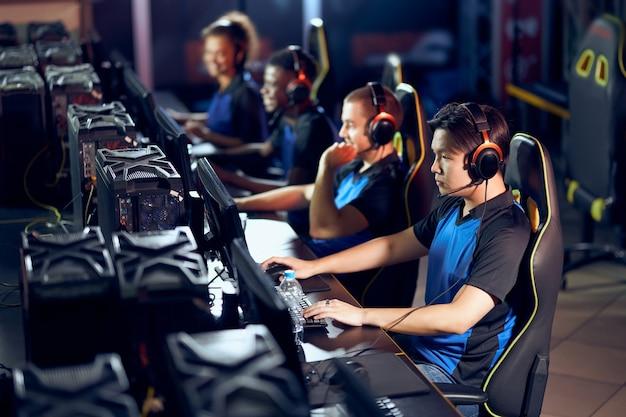 Grać by wygrać. wielorasowy zespół profesjonalnych graczy cybersportowych w słuchawkach biorących udział w globalnym turnieju esportowym, grających w gry wideo online, widok z boku