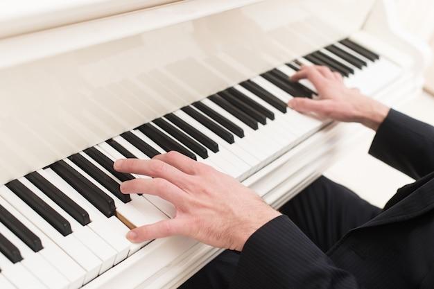 Grać na pianinie. zbliżenie z góry na człowieka grającego na pianinie