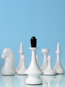 Grać w szachy. biała królowa na tle pozostałych postaci