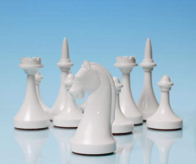 Grać w szachy. biały rycerz na tle pozostałych postaci