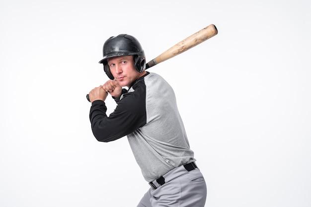 Gracz baseballa pozuje w hełmie z nietoperzem