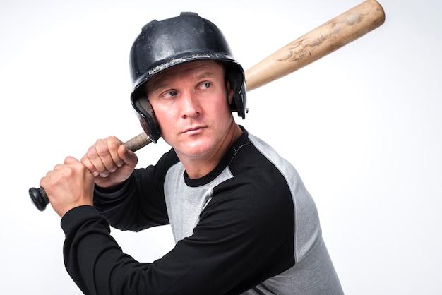 Gracz baseballa pozuje z nietoperzem i hełmem