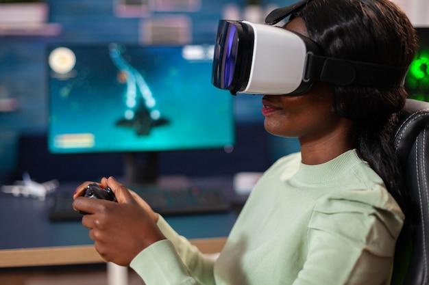 Gracz e-sportowy korzystający z zestawu słuchawkowego vr w rywalizacji na żywo z bezprzewodowym kontrolerem. mistrzostwa w wirtualnej strzelance kosmicznej w cyberprzestrzeni, gracz e-sportowy występujący na komputerze podczas turnieju gier.