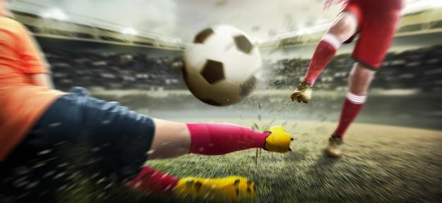 Gracz futbolu mężczyzna kopie piłkę, gdy jego przeciwnik próbuje uporać się z piłką