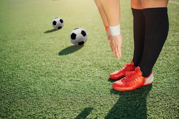 Gracz futbolu stoi na trawniku i rozciąga się do zielonego pola. trzyma nogi i ręce razem. dwie leżące dalej piłki.