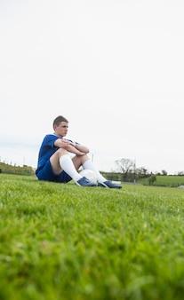 Gracz futbolu w błękicie bierze przerwę na boisku