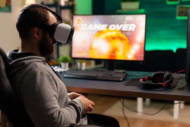 Gracz gier wideo przegrywa rywalizację w kosmicznej strzelance podczas noszenia zestawu wirtualnej rzeczywistości. pokonany gracz korzystający z profesjonalnej konsoli do turnieju online późno w nocy w pokoju gier