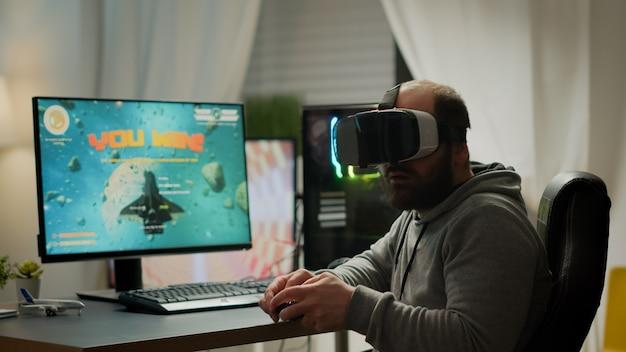 Gracz gier wideo z goglami vr podnoszącymi ręce po wygraniu konkursu kosmicznej strzelanki. profesjonalny gracz grający w gry wideo online z nową grafiką na potężnym komputerze z pokoju gier