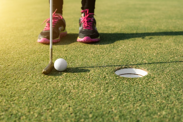 Gracz golfa przy kładzeniem zieleni kładzenia piłka golfowa w dziurę. koncepcja sportu golfa.