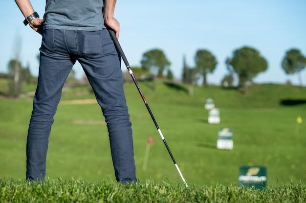 Gracz golfa z czapką opiera na kiju golfowym patrzeje kurs