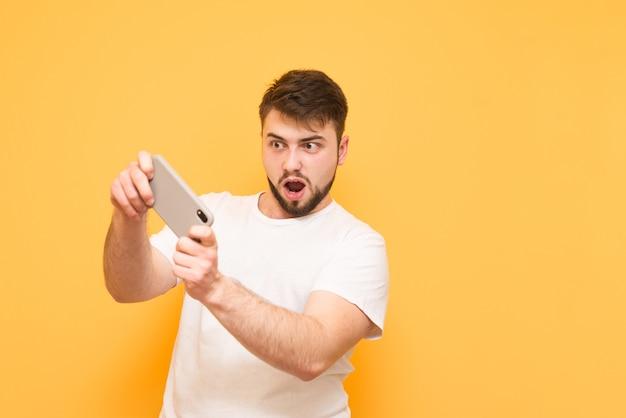 Gracz gra w gry wideo na smartfonie, koncentruje się na ekranie, na białym tle