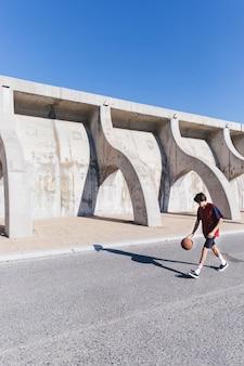 Gracz gra w koszykówkę blisko otaczającej ściany