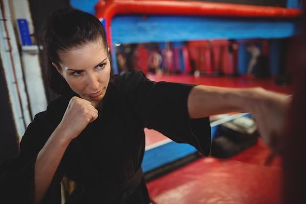 Gracz karate ćwiczy boks z workiem treningowym