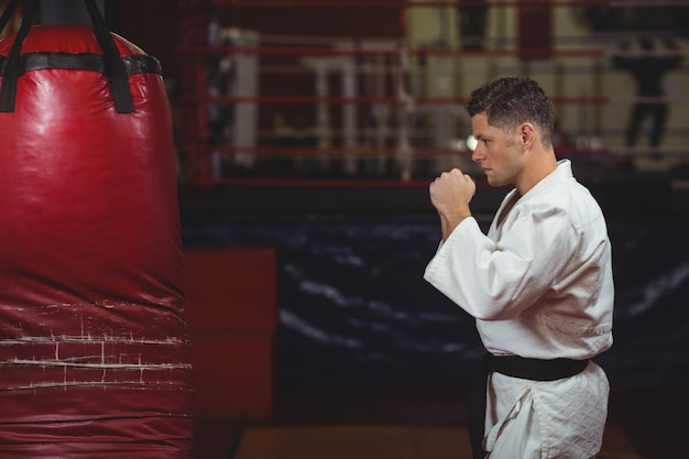 Gracz karate ćwiczy na worku treningowym
