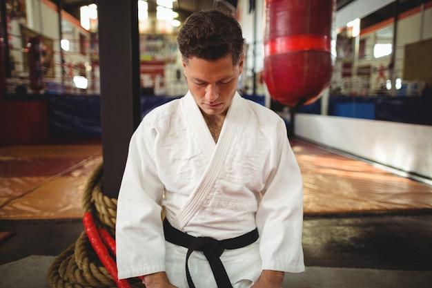 Gracz karate siedzi w pozycji seiza
