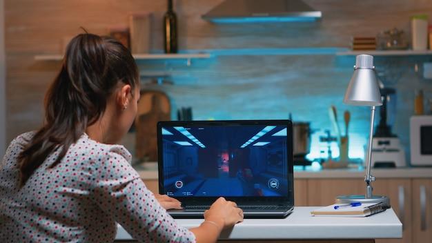 Gracz kobieta siedzi w domu w kuchni testuje nową grę na profesjonalnym laptopie. zmęczony gracz gra w gry wideo online na swoim komputerze osobistym z nowoczesną siecią bezprzewodową