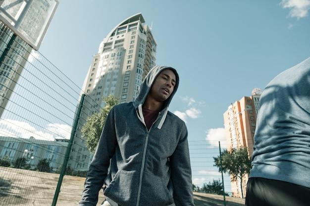 Gracz koszykówki. ładny afro amerykanin ubrany w strój sportowy podczas gry w koszykówkę
