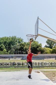 Gracz koszykówki miotania piłka w obręczu przy outdoors sądem